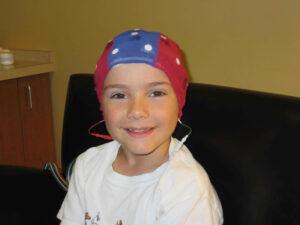 Smiling Boy Wearing a Brain Map (QEEG) Cap